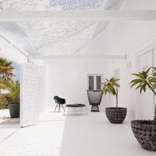 Immagine di una porta d'ingresso mediterranea di medie dimensioni con pareti bianche, una porta a due ante, una porta bianca e pavimento bianco
