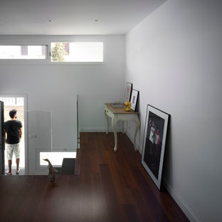 Small minimalist dark wood floor entryway photo in Seville with white walls and a white front door