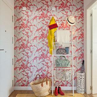 Idee per una piccola porta d'ingresso eclettica con pavimento in legno massello medio, pareti rosa, una porta singola e una porta bianca