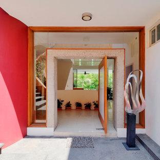 他の地域の大きい回転式ドアコンテンポラリースタイルのおしゃれな玄関 (ピンクの壁、ライムストーンの床、ガラスドア) の写真