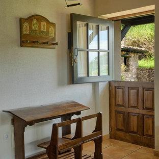 Modelo de puerta principal rústica, pequeña, con puerta tipo holandesa, puerta de madera en tonos medios, paredes blancas, suelo de baldosas de terracota y suelo rojo