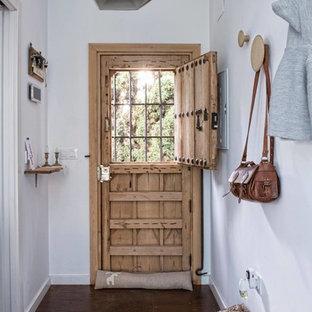 Diseño de hall bohemio con paredes blancas, suelo de madera oscura, puerta tipo holandesa y puerta de madera clara