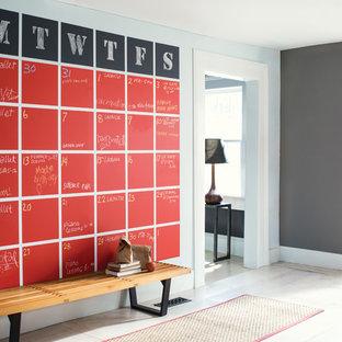 Cette image montre une entrée design avec un couloir, un mur gris, une porte blanche et un sol beige.