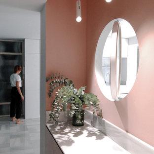 Идея дизайна: вестибюль среднего размера в стиле модернизм с розовыми стенами, мраморным полом, поворотной входной дверью, входной дверью из светлого дерева и серым полом