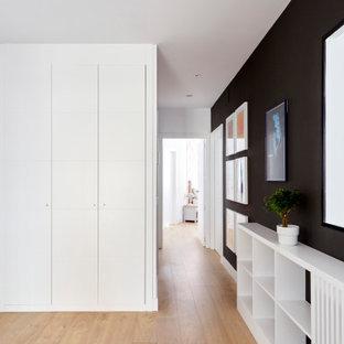 マドリードの中くらいのモダンスタイルのおしゃれな玄関ロビー (黒い壁、淡色無垢フローリング、白いドア) の写真