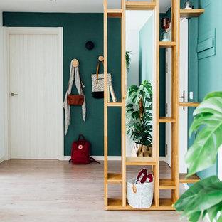 Modelo de vestíbulo nórdico, grande, con paredes verdes, suelo de madera clara, puerta simple, suelo marrón y puerta blanca