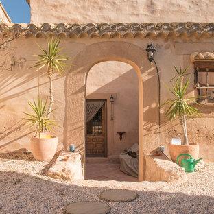Diseño de puerta principal mediterránea con paredes beige, puerta simple y puerta de madera en tonos medios