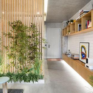 Esempio di un ingresso o corridoio industriale con pareti bianche, pavimento in cemento, una porta singola, una porta bianca e pavimento grigio
