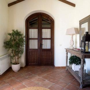 Ejemplo de vestíbulo campestre, extra grande, con paredes verdes, suelo de baldosas de terracota, puerta doble, puerta de madera oscura y suelo marrón