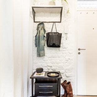 Example of a small danish beige floor entryway design in Madrid with white walls and a white front door