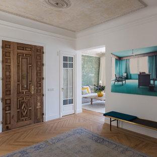 Imagen de distribuidor actual con suelo de madera en tonos medios, puerta doble, puerta de madera oscura, paredes blancas y suelo beige