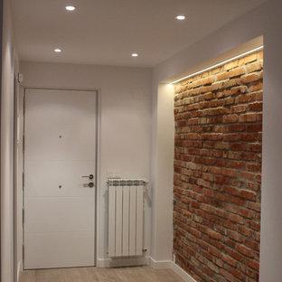 Bild på en liten industriell hall, med ljust trägolv, en enkeldörr och en vit dörr
