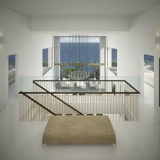 Idée de décoration pour un grand vestibule minimaliste avec un mur blanc, béton au sol, une porte pivot, un sol gris et un plafond décaissé.