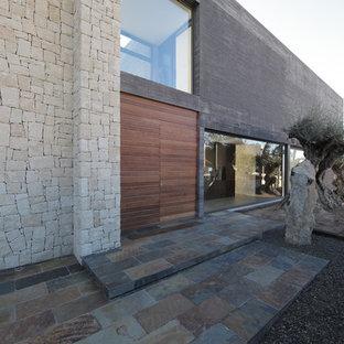 Modelo de puerta principal actual, grande, con paredes grises, suelo de pizarra, puerta doble y puerta de madera en tonos medios