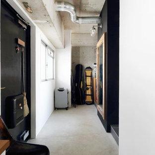 東京23区の片開きドアインダストリアルスタイルのおしゃれな玄関 (白い壁、コンクリートの床、黒いドア、グレーの床) の写真