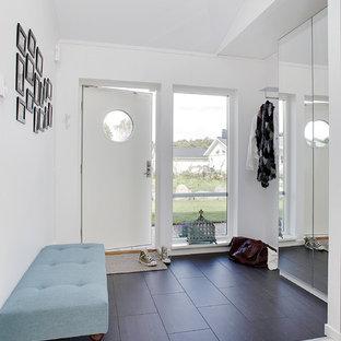 Réalisation d'une entrée nordique de taille moyenne avec un mur blanc, un sol en bois foncé, une porte simple, une porte blanche et un couloir.