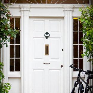 Klassisk inredning av en ingång och ytterdörr, med en enkeldörr och en vit dörr