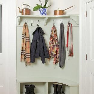 Cette image montre une petit entrée traditionnelle avec un vestiaire, un mur vert, un sol en bois clair et une porte simple.