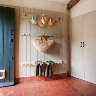 Example of a mid-sized cottage terra-cotta floor and orange floor entryway design in Kent with beige walls and a blue front door
