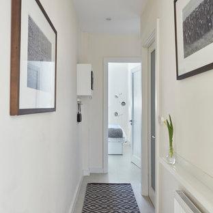 Idées déco pour une entrée scandinave de taille moyenne avec un couloir, un mur blanc, un sol en vinyl, une porte simple, une porte en bois brun et un sol blanc.