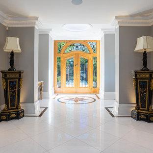 Esempio di un grande corridoio design con pareti grigie, una porta a due ante, una porta in legno bruno, pavimento bianco e pavimento in marmo