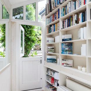 ロンドンのダッチドアシャビーシック調のおしゃれな玄関 (白い壁、塗装フローリング、白いドア) の写真