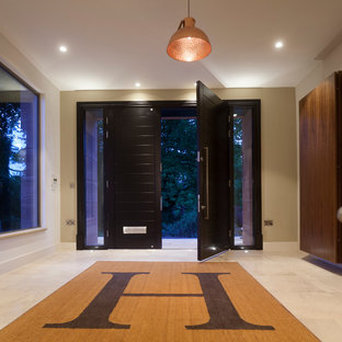 Esempio di una grande porta d'ingresso contemporanea con pareti verdi, pavimento in pietra calcarea, una porta a due ante e una porta nera