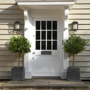 Exemple d'une porte d'entrée nature avec une porte simple, une porte blanche et un mur beige.