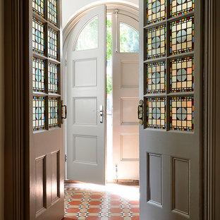 サリーの中くらいの両開きドアヴィクトリアン調のおしゃれな玄関ラウンジ (白い壁、テラコッタタイルの床、白いドア) の写真