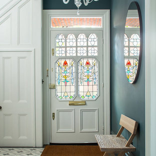 Photo of a traditional entrance in London with blue walls, a single front door, a white front door and multi-coloured floors.