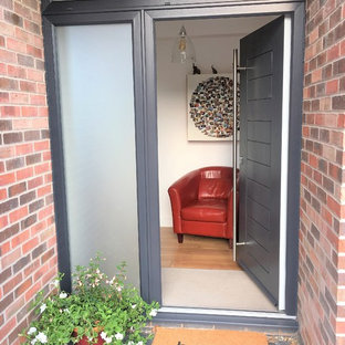 Inspiration for a mid-sized modern carpeted entryway remodel in Other with a gray front door