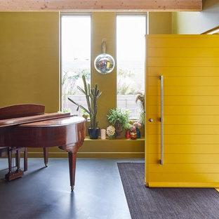 バッキンガムシャーの中サイズの片開きドアエクレクティックスタイルのおしゃれな玄関ロビー (黄色い壁、リノリウムの床、黄色いドア、黒い床) の写真