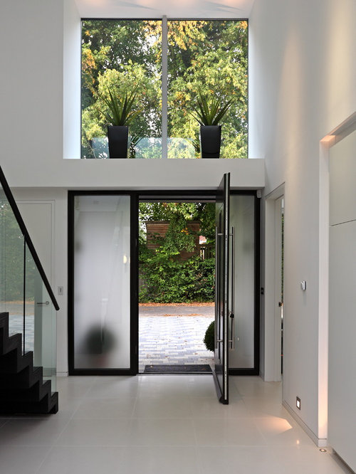 Example Of A Trendy White Floor Entryway Design In Other With White Walls  And A Glass