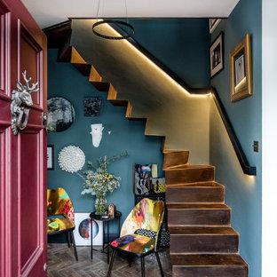 Inspiration för små eklektiska hallar, med blå väggar, mellanmörkt trägolv, en enkeldörr, en röd dörr och brunt golv