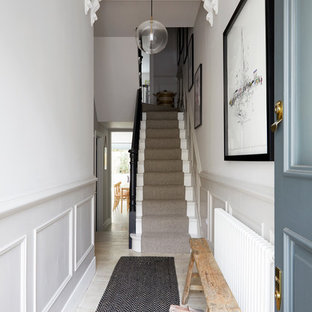 Bild på en mellanstor nordisk hall, med vita väggar, målat trägolv, en enkeldörr, en blå dörr och beiget golv