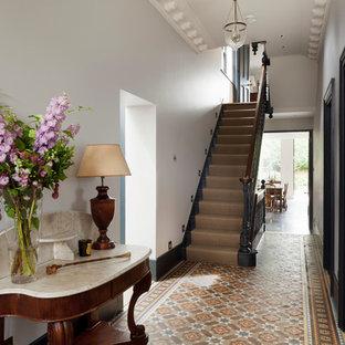 Inspiration för klassiska entréer, med vita väggar och flerfärgat golv