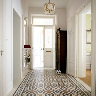 Photo of a traditional hallway in London with white walls and a white front door.