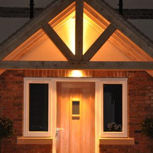 ウィルトシャーの大きい片開きドアカントリー風おしゃれな玄関ドア (赤い壁、トラバーチンの床、木目調のドア) の写真