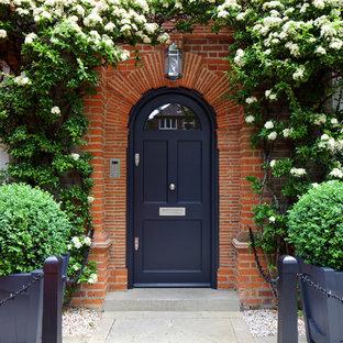 ロンドンの片開きドアトラディショナルスタイルのおしゃれな玄関ドア (赤い壁、コンクリートの床、黒いドア、グレーの床) の写真