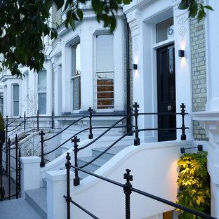ロンドンの大きい片開きドアコンテンポラリースタイルのおしゃれな玄関ドア (白い壁、ライムストーンの床、黒いドア、グレーの床) の写真