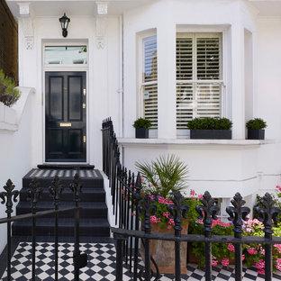 Свежая идея для дизайна: входная дверь в викторианском стиле с белыми стенами, одностворчатой входной дверью и черной входной дверью - отличное фото интерьера