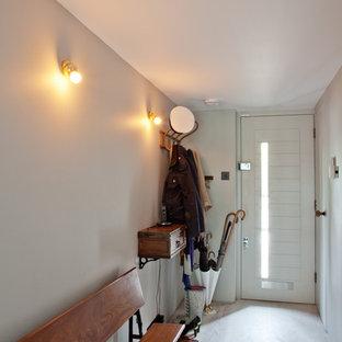 Foto på ett funkis kapprum, med grå väggar, en enkeldörr och en vit dörr