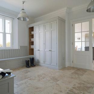 Inredning av en klassisk mellanstor entré, med vita väggar och travertin golv