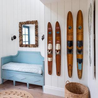 На фото: большая узкая прихожая в морском стиле с желтыми стенами, паркетным полом среднего тона, одностворчатой входной дверью, синей входной дверью, коричневым полом, потолком из вагонки и панелями на части стены