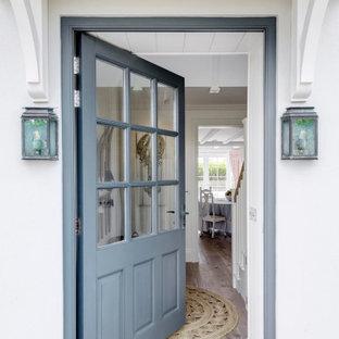 Aménagement d'une grand entrée bord de mer avec un couloir, un mur jaune, un sol en bois brun, une porte simple, une porte bleue, un sol marron, un plafond en lambris de bois et du lambris.