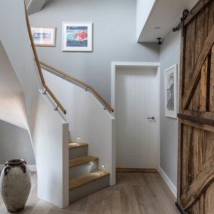 Diseño de hall costero, grande, con paredes grises, suelo de madera clara, puerta corredera, puerta de madera en tonos medios y suelo gris
