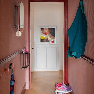 Cette image montre une petit entrée design avec un mur rose, un sol en bois brun, un couloir et un sol marron.