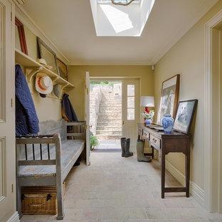 Idee per un corridoio country con pareti beige, pavimento in terracotta, una porta singola, una porta bianca e pavimento beige