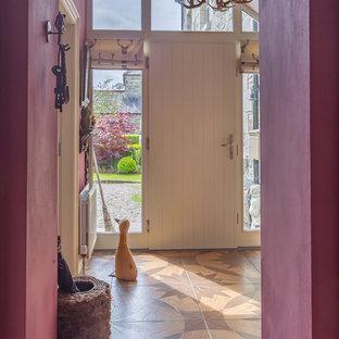 На фото: прихожая в стиле кантри с фиолетовыми стенами, полом из керамической плитки, одностворчатой входной дверью, белой входной дверью и коричневым полом с