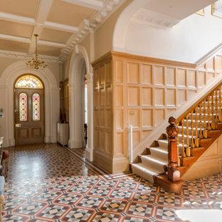 ロンドンの片開きドアトラディショナルスタイルのおしゃれな玄関ロビー (ベージュの壁、木目調のドア、マルチカラーの床、格子天井、パネル壁) の写真